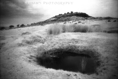 The iconic Cheesewring sits atop Stowe's Hill on Bodmin Moor, Cornwall, England. Infrared film photograph shot on Kodak HIE-135 infrared film in 2008.